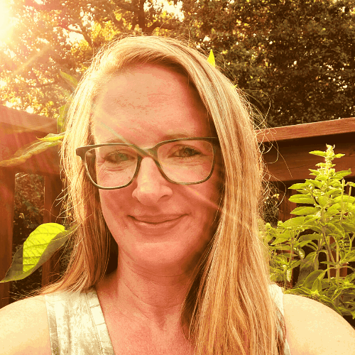 Headshot of woman with blond hair in sunlight surrounded by plants in a container garden